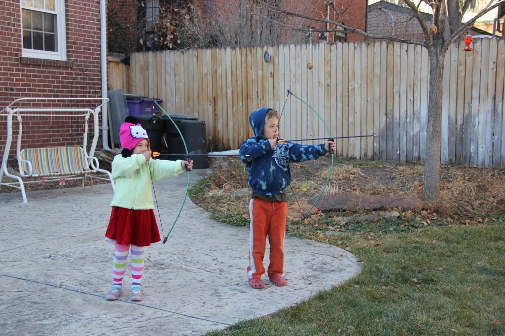 Jude and Anna line up their bow and arrows in the backyard