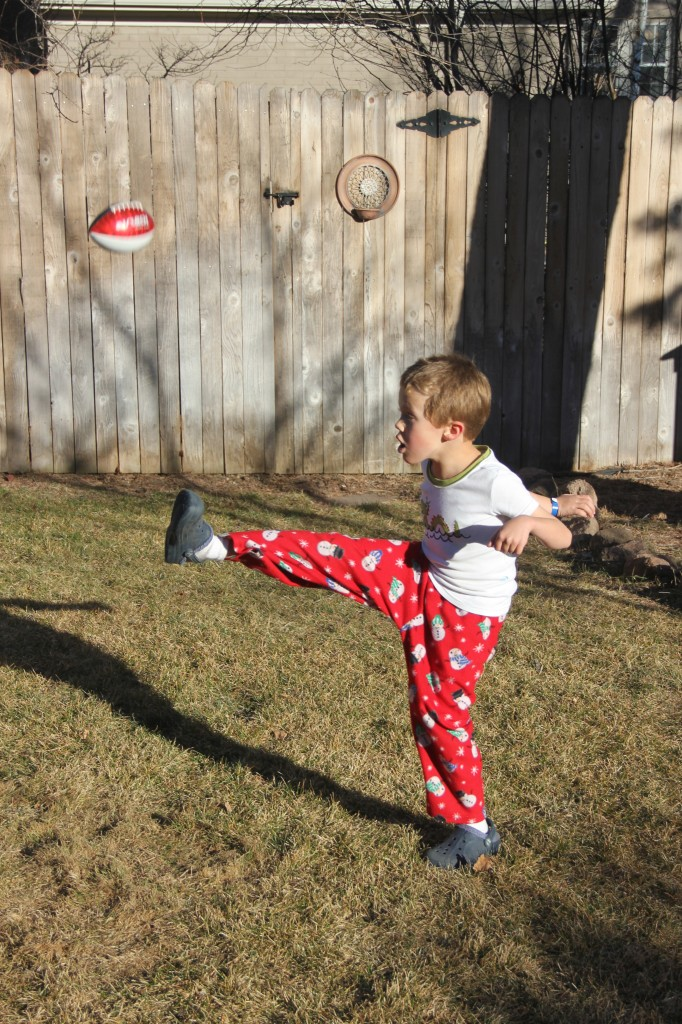 Jude practicing his punting in the backyard