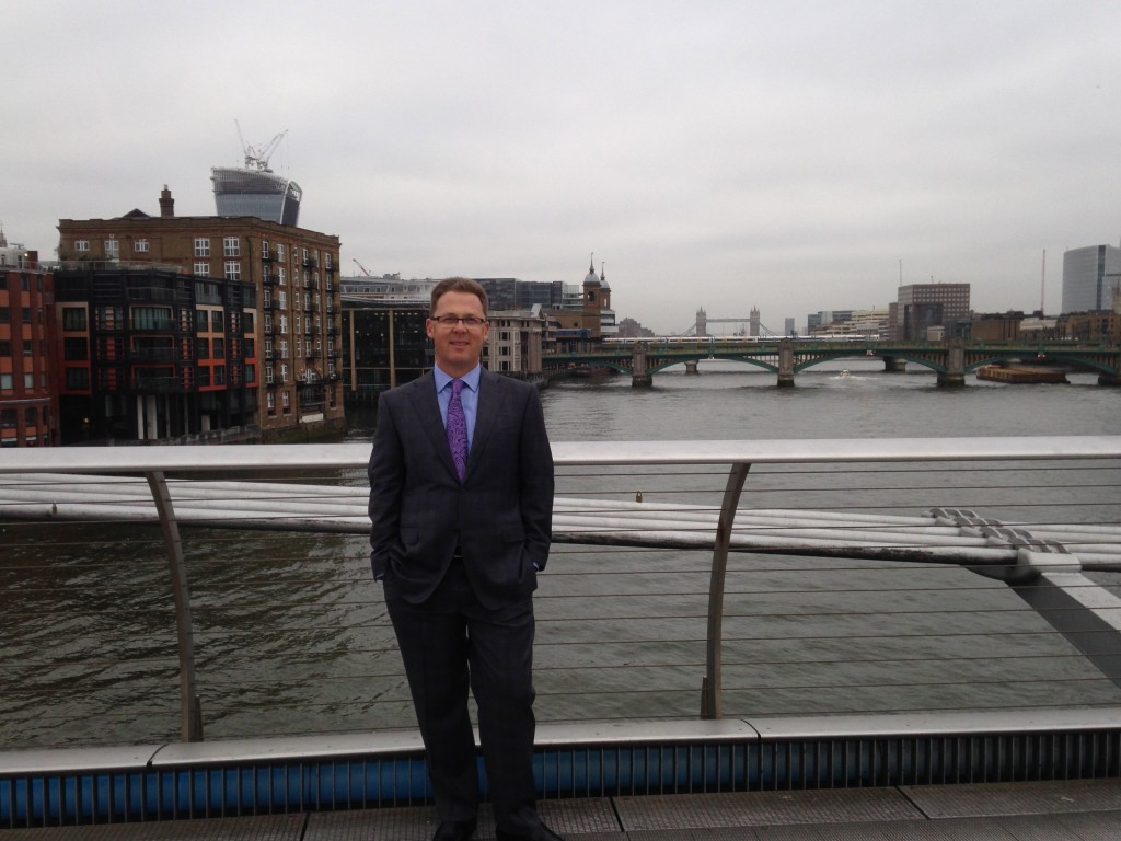 In London on the pedestrian bridge over the Thames with  London Bridge in the background