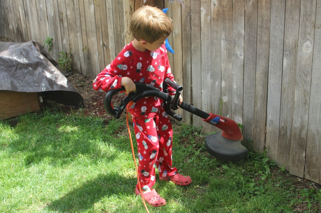 Jude working the weed whacker in the backyard