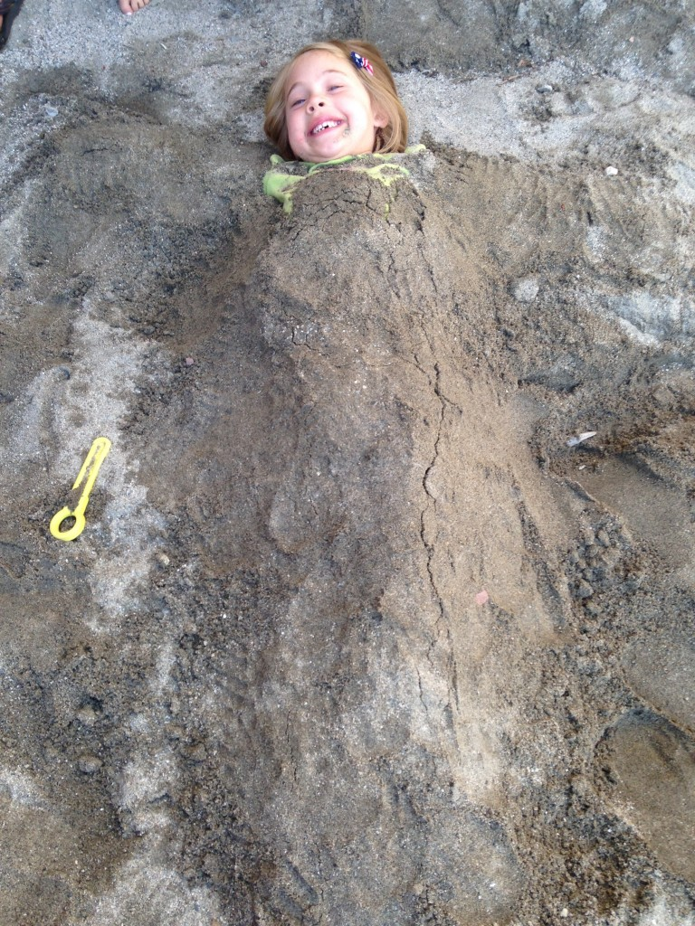 Anna in the sandbox at the Mexican restaurant - buried by her cousins