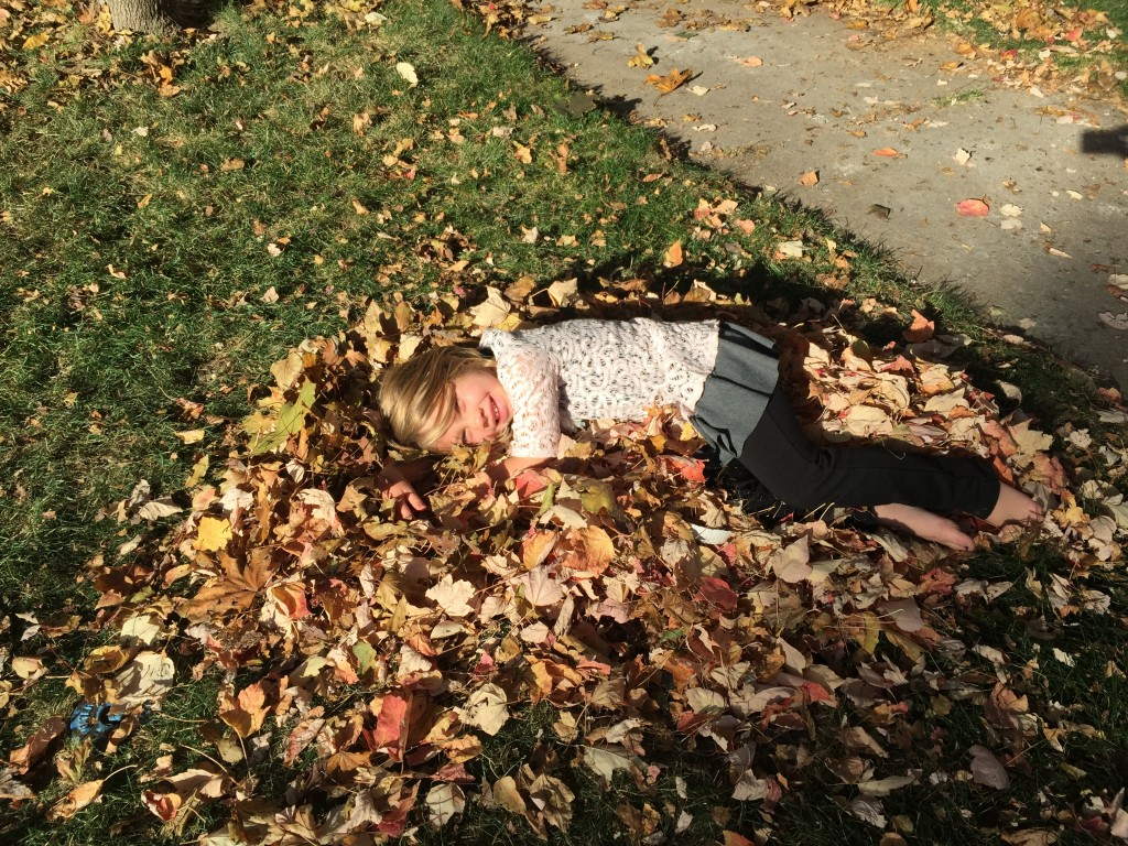 Anna enjoying the fruits of her labor after raking a pile of leaves