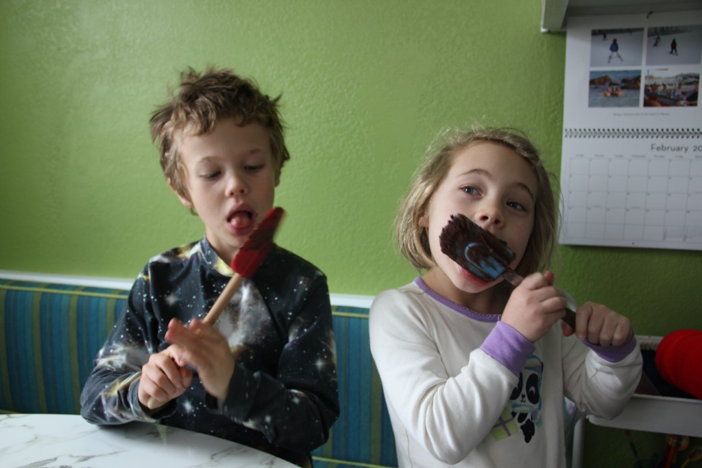 Jude and Anna licking the spatula clean after Marcy made brownies