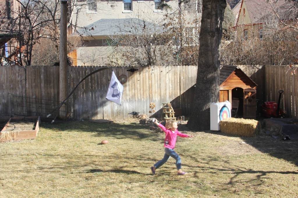 Anna trying to fly a kite in our backyard