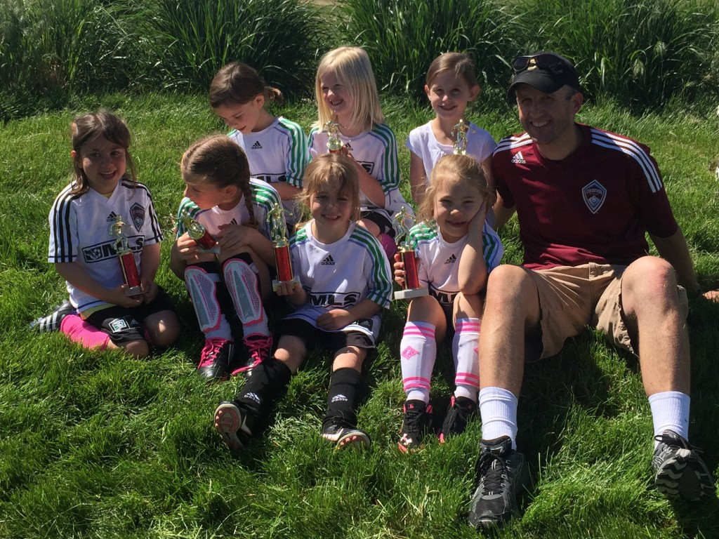 Anna's soccer team with Coach Matt showing off their trophies