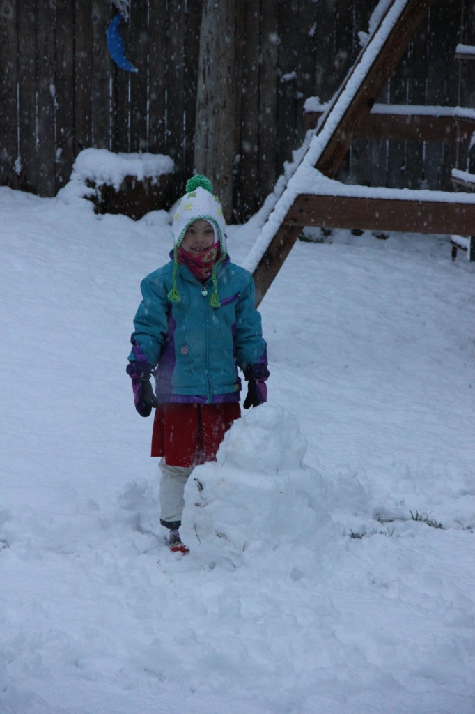 Anna building a snowman in the back yard