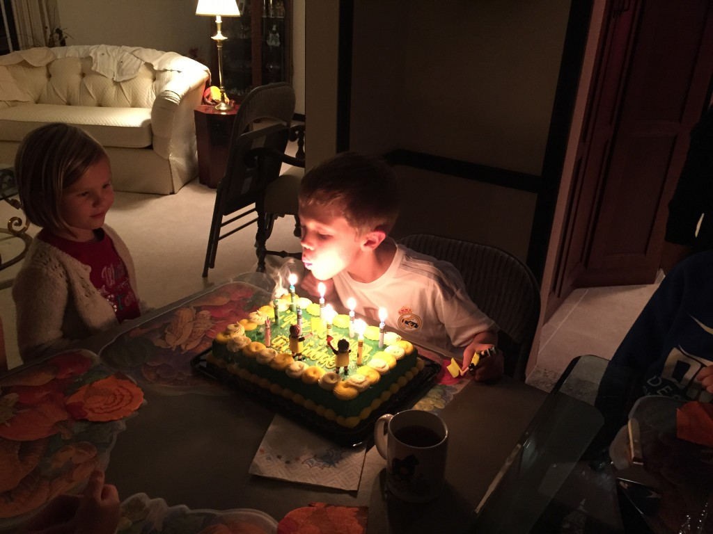 Jude blowing out his 9 candles with Ella looking on