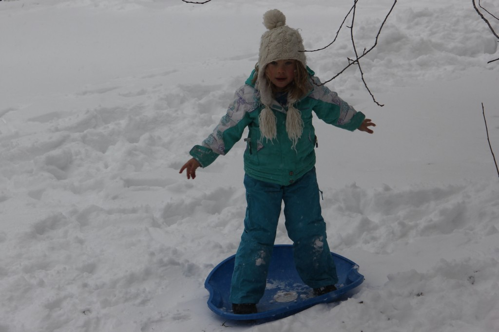 """Anna """"snowboarding"""" on a sled in our front yard"""