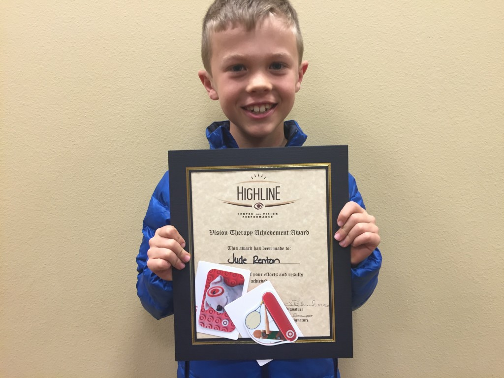 Jude proudly shows off his graduation certificate from vision therapy