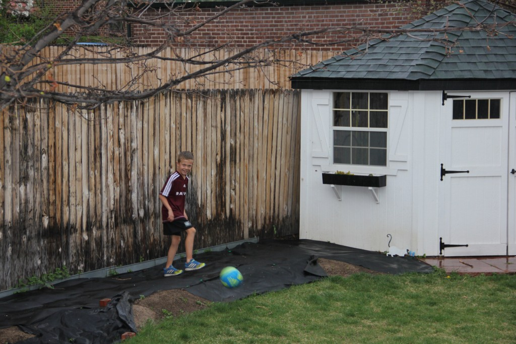 Jude playing soccer in the backyard in the pouring rain