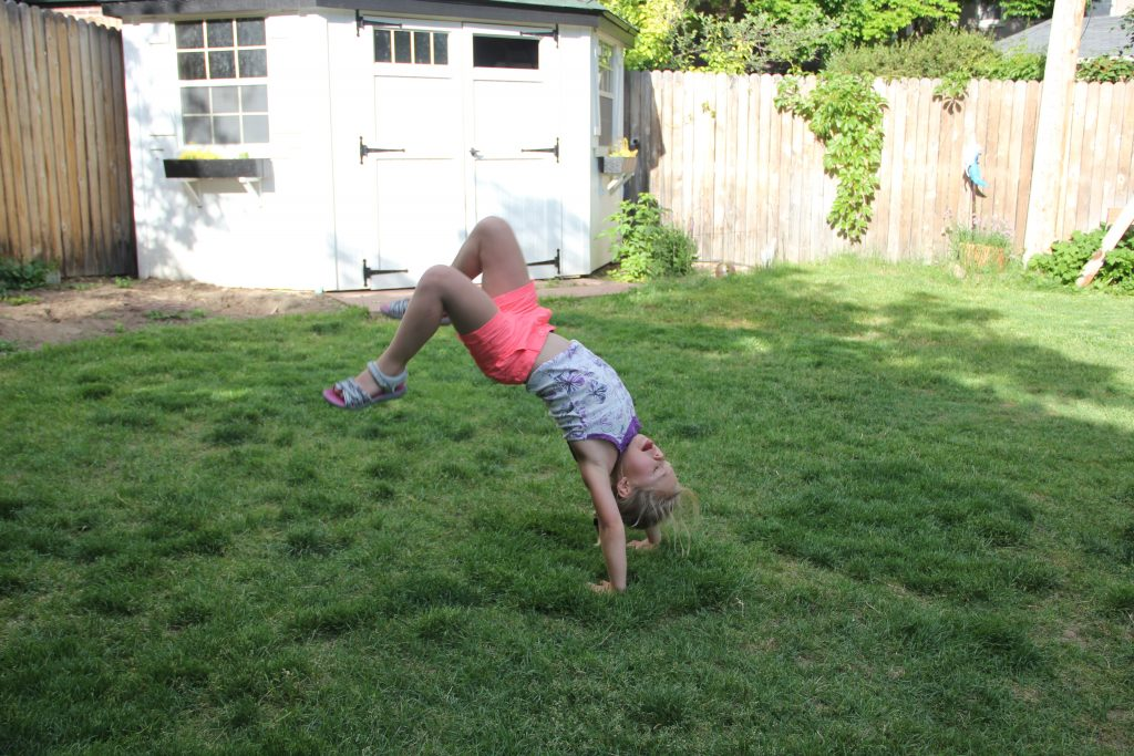 Anna doing hand stands and back flips in the backyard