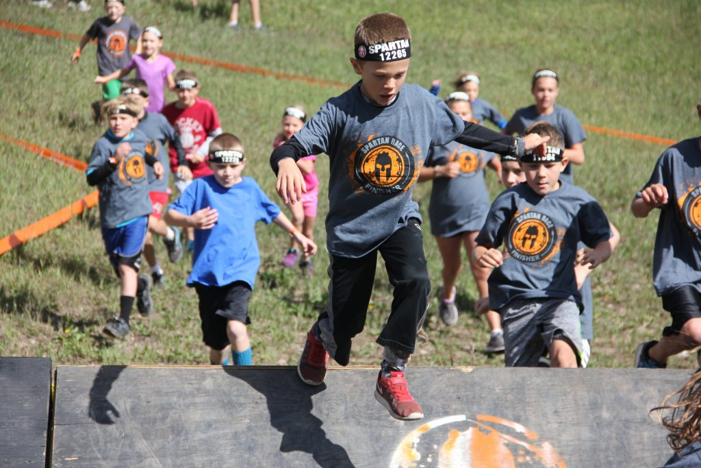 Jude flying over obstacles in the kids Spartan race