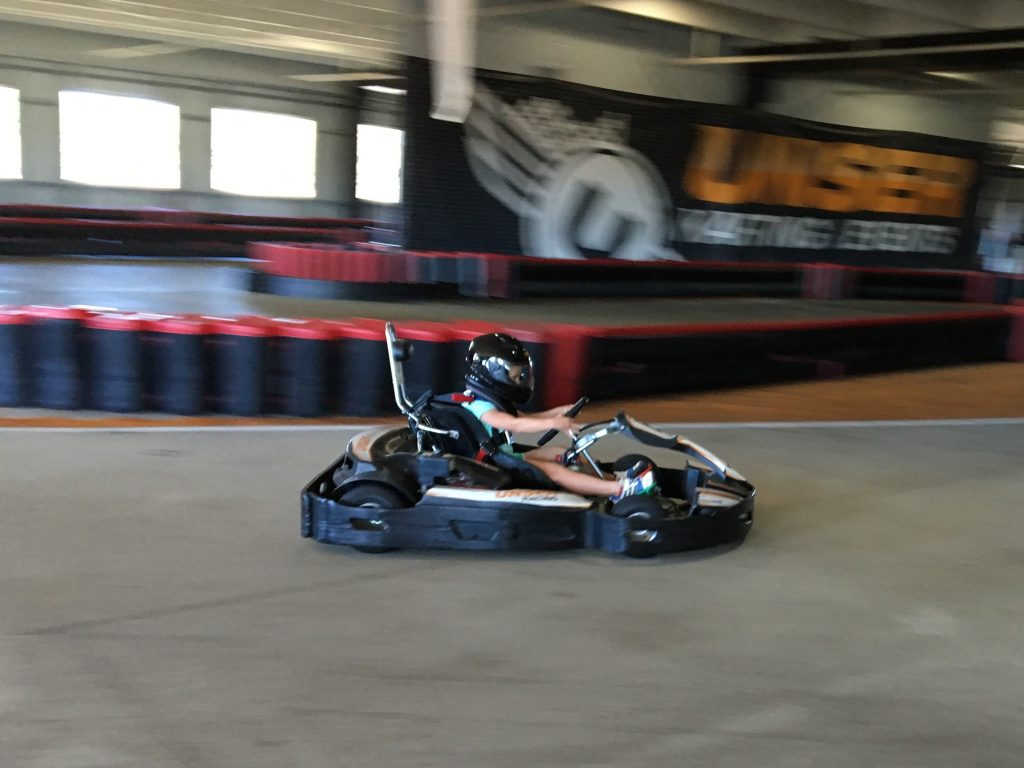 Anna driving a go-kart at the indoor track