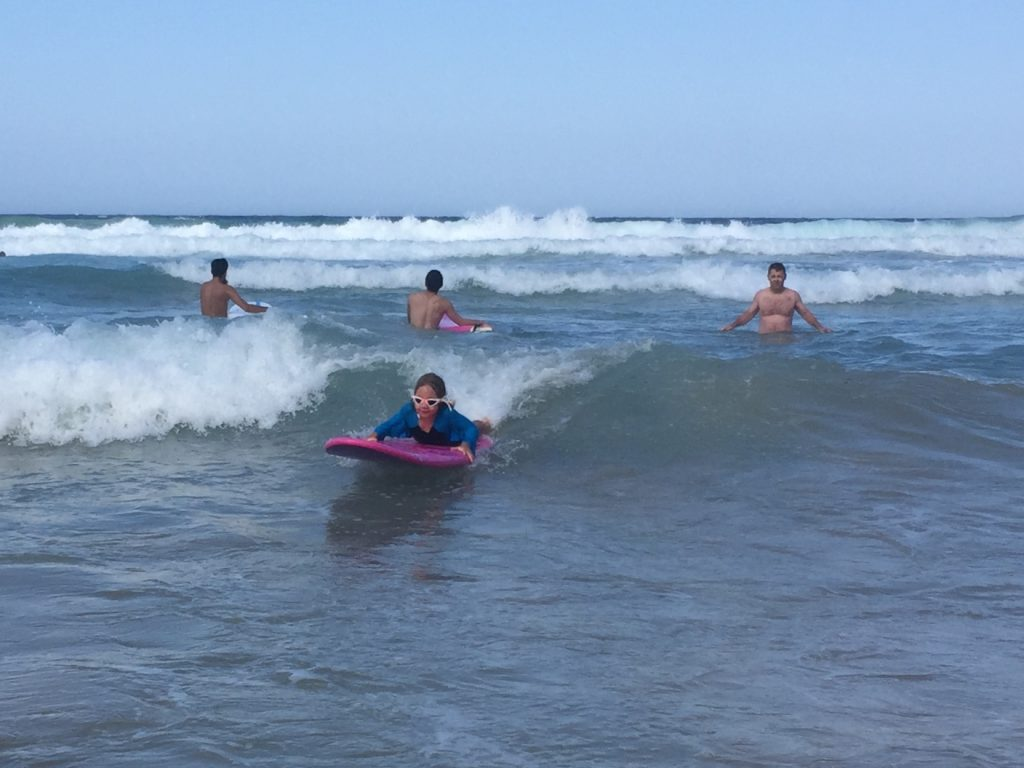 Anna catching a wave on a surfboard for the first time