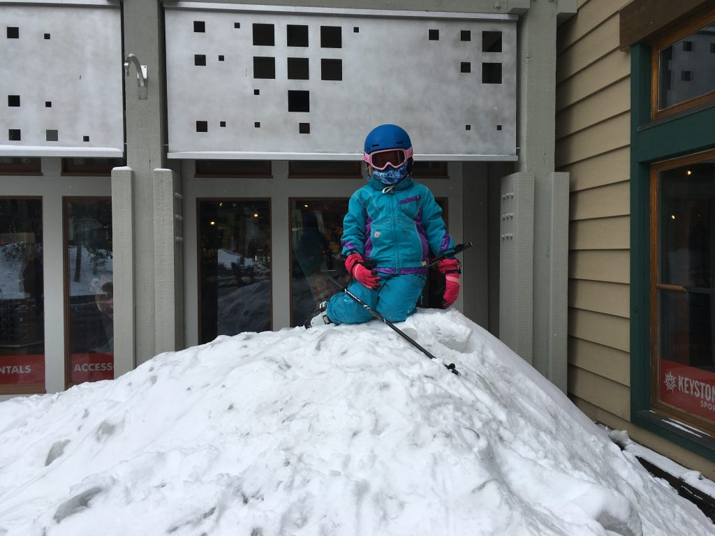Anna on a pile of snow at the bottom of Keystone Mountain