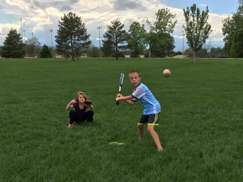 Jude and Anna playing a focused game of baseball in the park
