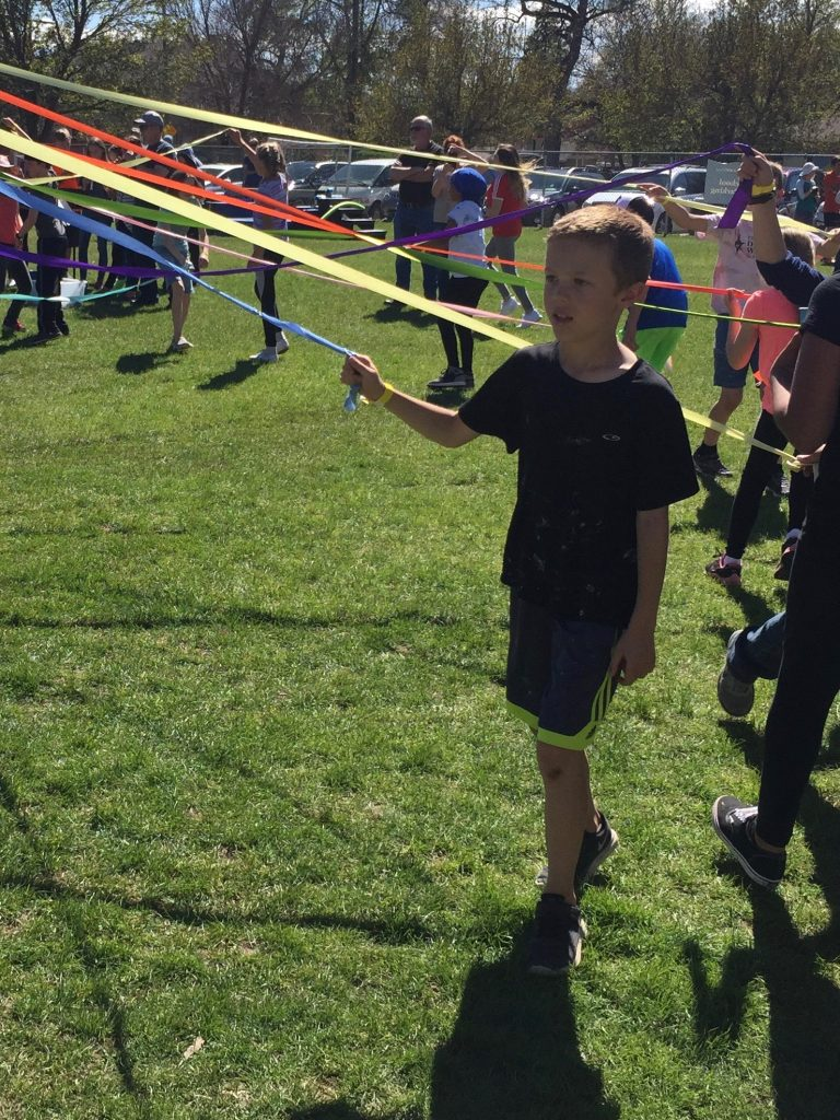 Jude walking around the Maypole at the school MayFest celebration
