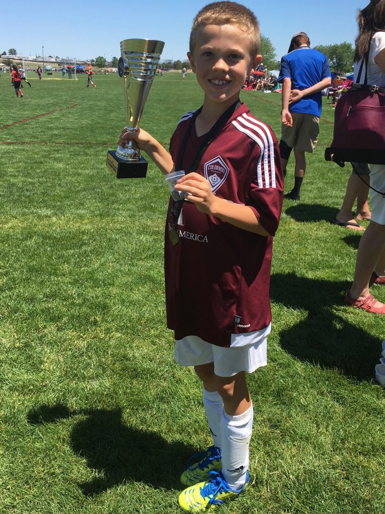 Jude with the team trophy after winning their soccer tournament