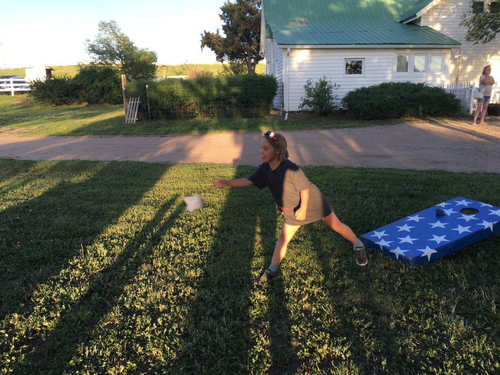 Anna playing the bean bag toss at the farm