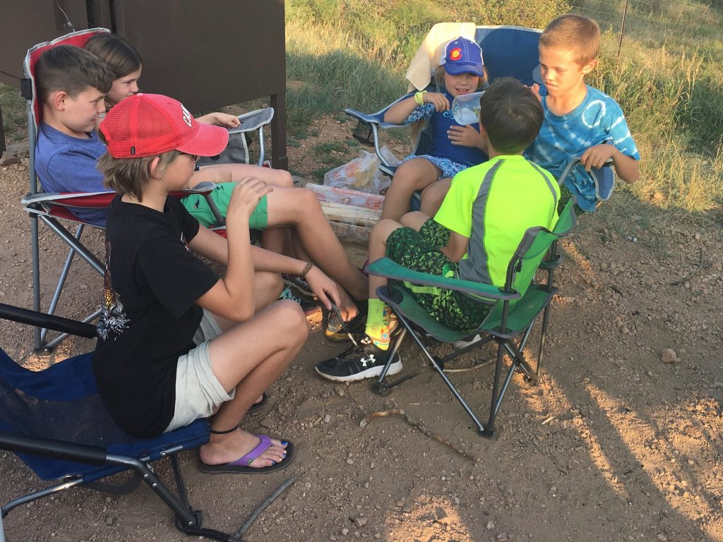 The kids playing a game of telephone at the campsite