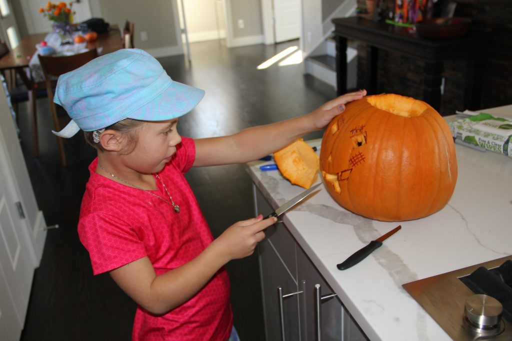 Anna carving her pumpkin in the kitchen