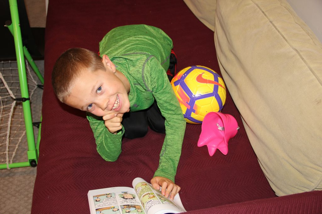 Jude reading his Big Nate book, taking a break from playing soccer in the basement