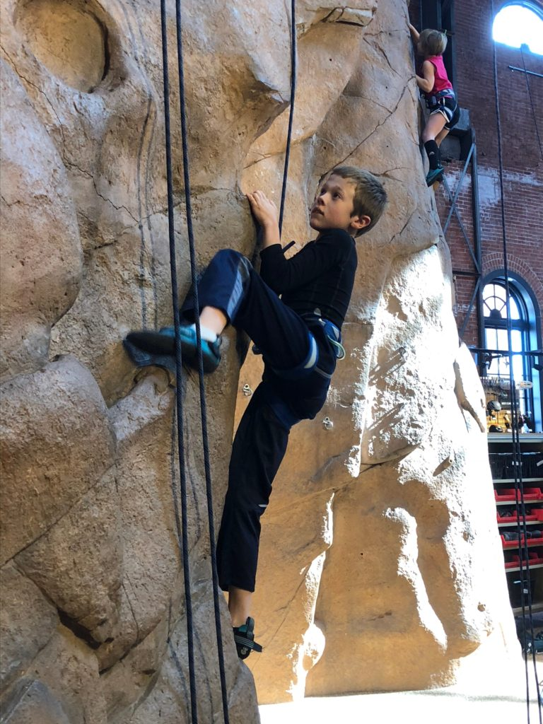 Jude and Anna tackle the climbing wall at REI